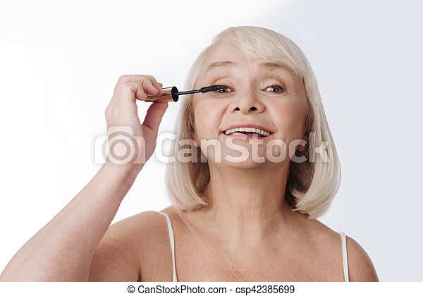 Delighted optimistic woman using a mascara brush - csp42385699