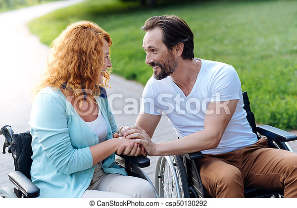Delighted senior couple having a walk in the wheelchairs - csp50130292