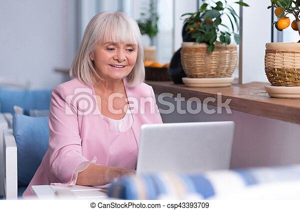 Delighted senior woman working - csp43393709