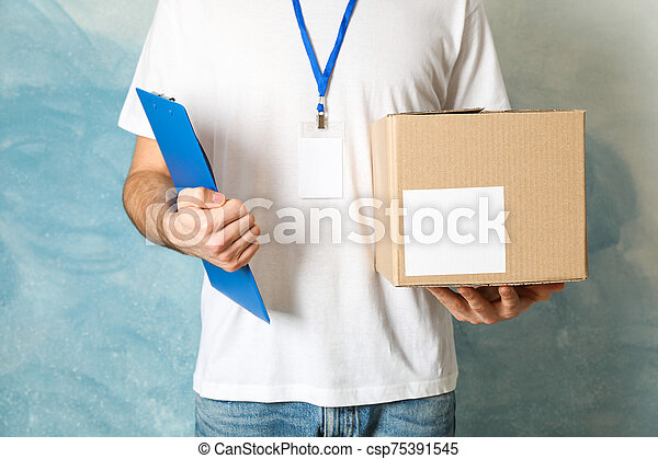Delivery man hold blank box and tablet against blue background, space for text - csp75391545