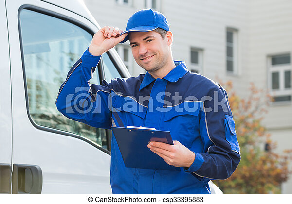Delivery Man In Uniform Holding Clipboard By Truck - csp33395883