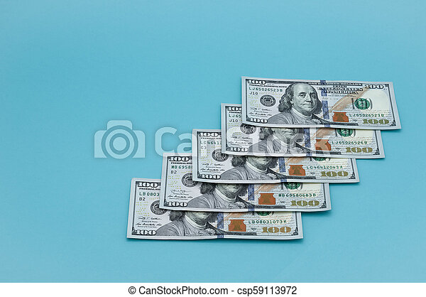 Denominations of one hundred American dollars on a blue background. - csp59113972