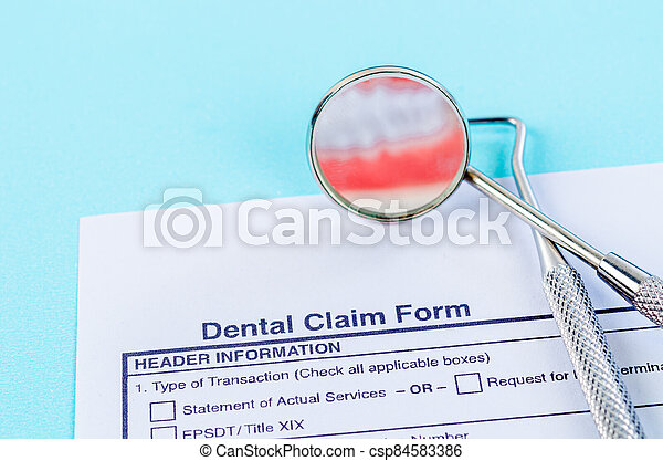 Dental claim Form with model tooth and dental instruments. - csp84583386
