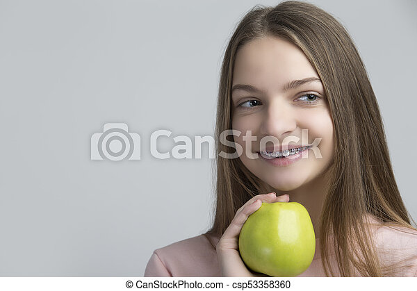 Dental Concepts. Portrait of Happy Teenage Female With Teeth Brackets. Posing With Green Apple and Smiling Against White - csp53358360