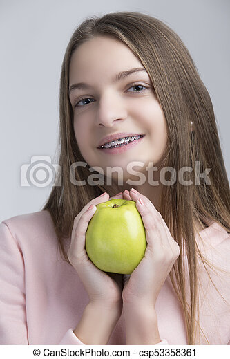 Dental Concepts. Portrait of Happy Teenage Female With Teeth Brackets. Posing With Green Apple and Smiling Against White. - csp53358361