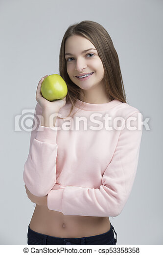 Dental Concepts. Portrait of Happy Teenage Female With Teeth Brackets. Posing With Green Apple and Smiling Against White. - csp53358358