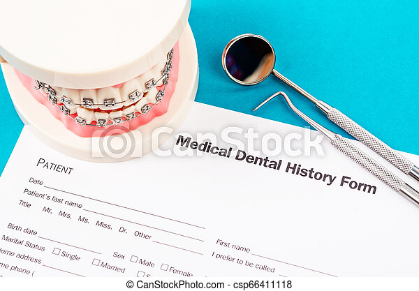 Dental history form with model tooth and dental instruments. - csp66411118