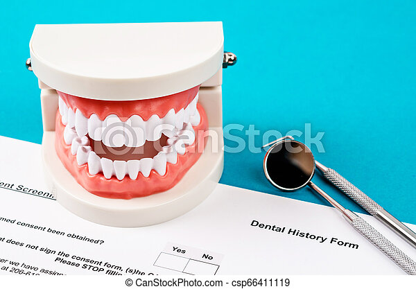 Dental history form with model tooth and dental instruments. - csp66411119