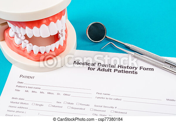Dental history form with model tooth and dental instruments. - csp77380184