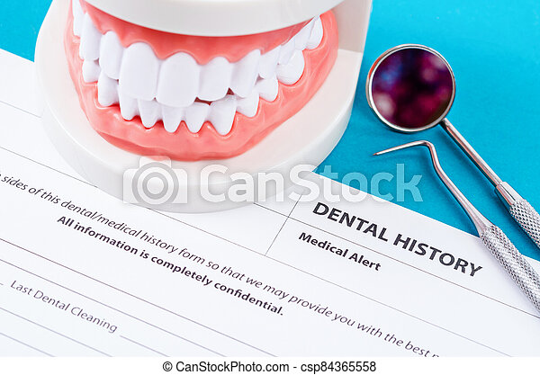 Dental history form with model tooth and dental instruments. - csp84365558