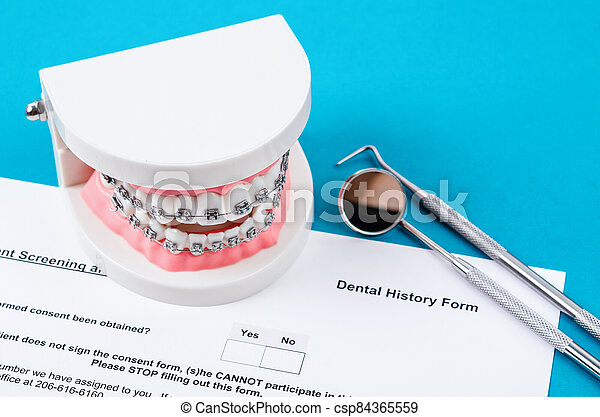 Dental History Form with model tooth and dental instruments. - csp84365559