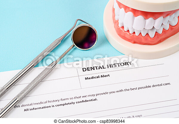 Dental history form with model tooth and dental instruments. - csp83998344