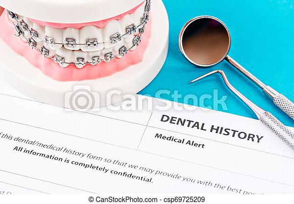 Dental history form with model tooth and dental instruments. - csp69725209