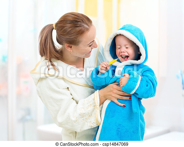 Dental hygiene in bathroom. Mother and child cleaning teeth together. - csp14847069