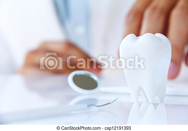 dentist holding molar - csp12191393