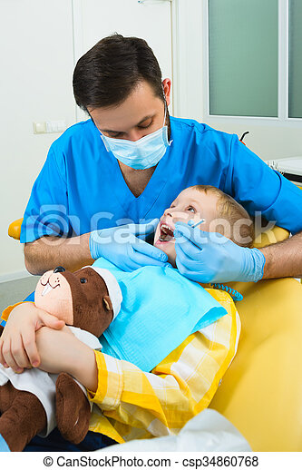 Dentist treats teeth of patient in dental clinic - csp34860768