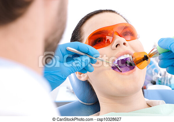 Dentist uses photopolymer lamp to cure teeth - csp10328627
