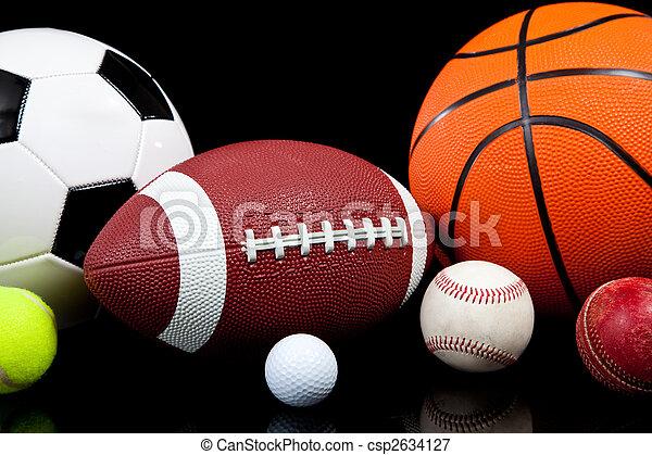 Varias bolas deportivas en un fondo negro - csp2634127