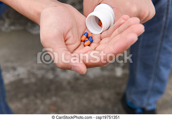 Depressed teenage boy with many tablets in hand, wants to take an overdose. concept of loneliness, misunderstanding, lack of integration - csp19751351