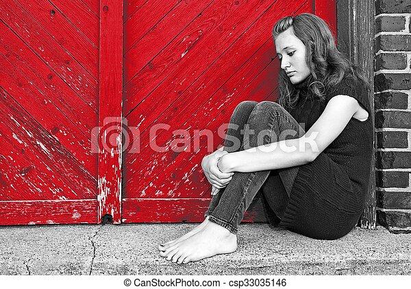 depressed teenage girl by red door - csp33035146