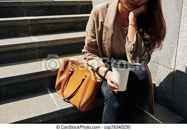 Depressed woman sitting on steps - csp76340230