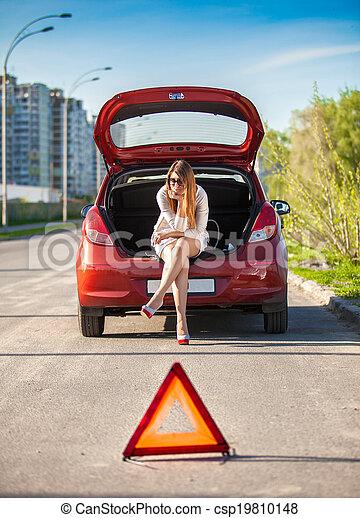 depressed woman sitting on trunk of broken car - csp19810148