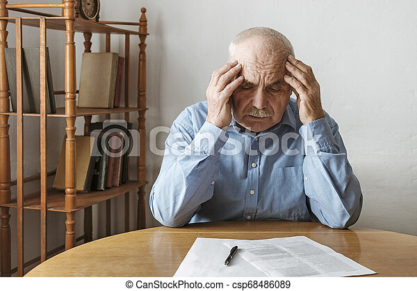 Depressed worried man looking at a form - csp68486089