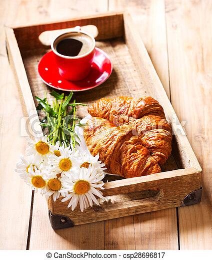 Bandeja de desayuno con croissants, taza de café y flores de margarita - csp28696817