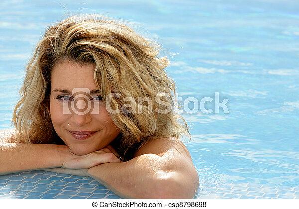 Mujer rubia descansando al borde de la piscina - csp8798698