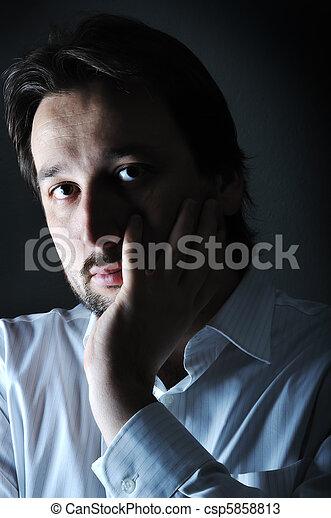 El primer plano del joven pensador descansando la barbilla en la palma, bajo llave - csp5858813