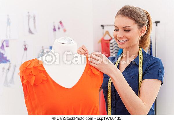 Designer at work. Beautiful female fashion designer adjusting dress on the mannequin and smiling - csp19766435