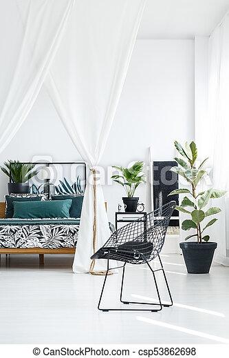Designer black chair in bedroom - csp53862698