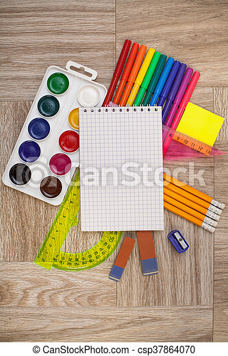 Desk, covered with multiple office supplies. Back to school composition - csp37864070