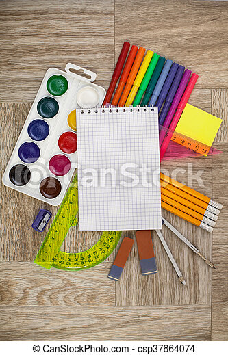 Desk, covered with multiple office supplies. Back to school composition - csp37864074