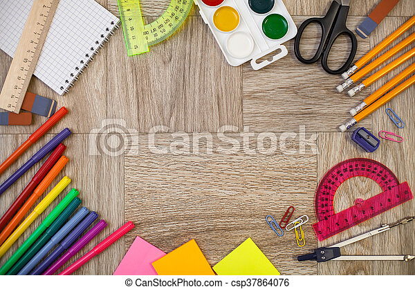 Desk, covered with multiple office supplies. Back to school composition - csp37864076