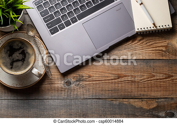 Desk with laptop, eye glasses, notepad, pen and a cup of coffee on a old wooden table. Top view with copy space. Flat lay. Dark background - csp60014884