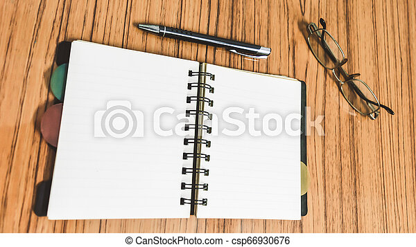 Desk with open notebook with blank pages, eye glasses and a pen. Business still life concept with office stuff on table. Education, working and planning concept. Selective focus with shallow DOF. - csp66930676