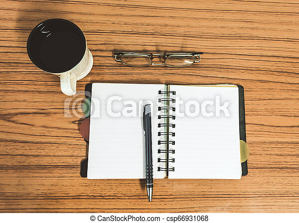 Desk with open notebook with blank pages, eye glasses, pen and a cup of coffee. Top view with copy space. Business still life concept with office stuff on table. Education, working or planning concept - csp66931068