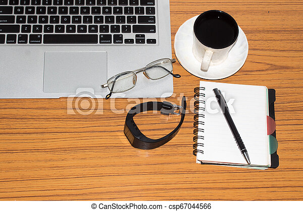Desk with open notebook with blank pages, eye glasses, pen and a cup of coffee. Top view with copy space. Business still life concept with office stuff on table. Education, working or planning concept - csp67044566