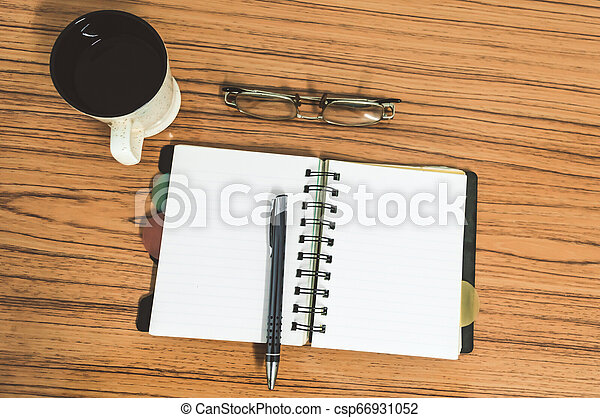 Desk with open notebook with blank pages, eye glasses, pen and a cup of coffee. Top view with copy space. Business still life concept with office stuff on table. Education, working or planning concept - csp66931052
