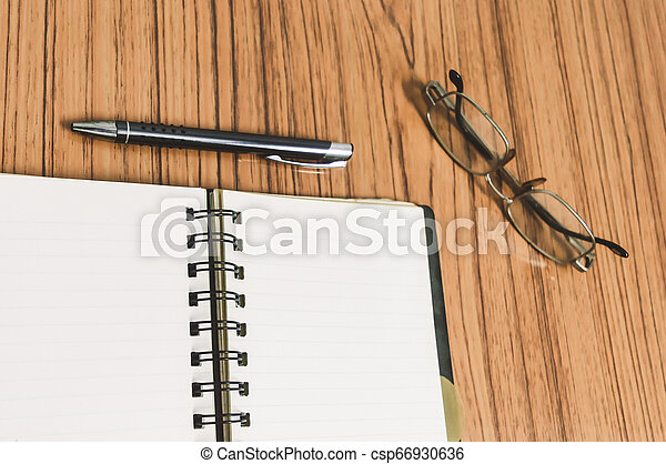Desk with open notebook with blank pages, eye glasses and a pen. Business still life concept with office stuff on table. Education, working and planning concept. Selective focus with shallow DOF. - csp66930636