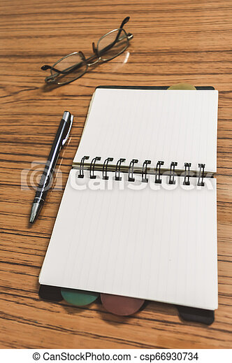 Desk with open notebook with blank pages, eye glasses and a pen. Business still life concept with office stuff on table. Education, working and planning concept. Selective focus with shallow DOF. - csp66930734