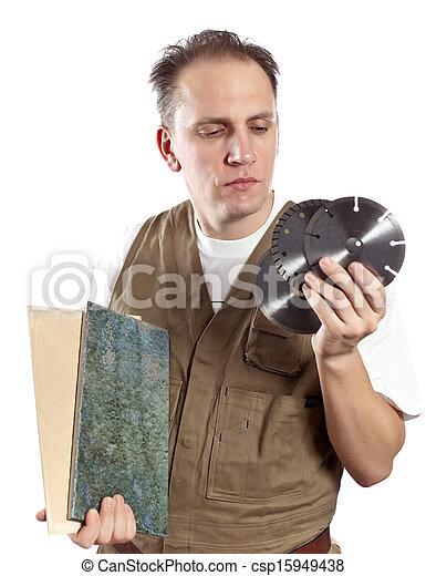 El hombre de overoles de trabajo elige un disco desmontable para la herramienta - csp15949438