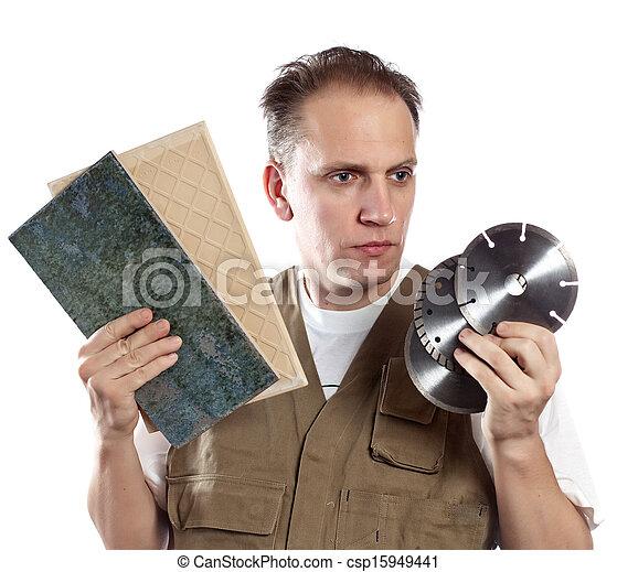 El hombre de overoles de trabajo elige un disco desmontable para la herramienta - csp15949441