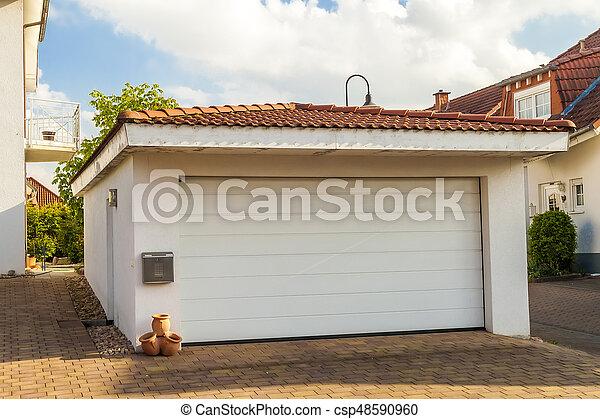 Detached white garage with orange brick tile roof - csp48590960