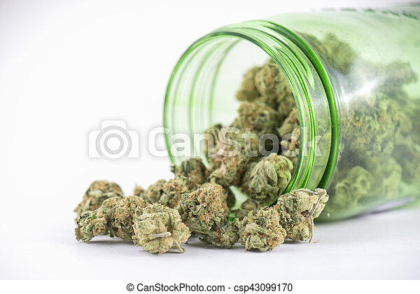 Detail of cannabis buds (ob reaper strain) on green glass jar isolated on white - csp43099170