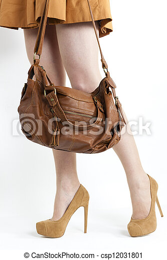 detail of standing woman wearing coat and brown pumps with a handbag - csp12031801