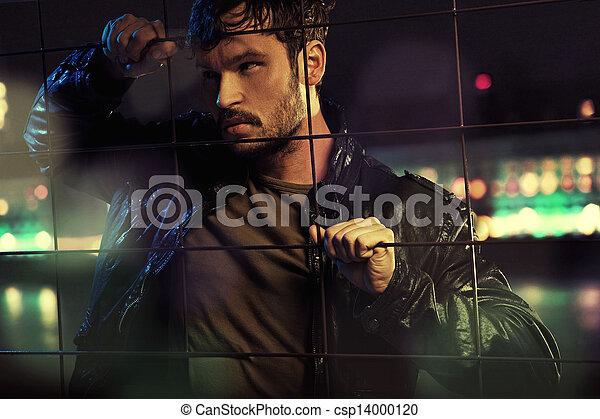 Hombre atractivo detrás de una valla metálica - csp14000120