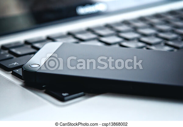 device technology. black phone and laptop keyboard - csp13868002