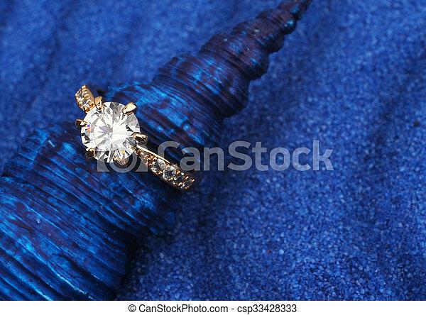 Foto de Macro de joyería con un gran diamante en concha azul y fondo de arena - csp33428333
